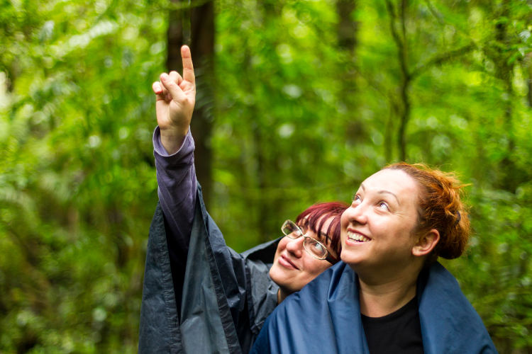 Group Of Two Adult Tourist Woman Into The Jungle Pointing To Left Upper Corner